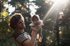 Der glückliche frohe Vater, der Spaß hat, wirft in der Luft sein Kind gegen den Solarstrahl - absichtlicher Sonnengreller glanz u Lizenzfreie Stockfotos