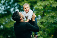 Der glückliche frohe Vater, der Spaß hat, wirft in der Luft sein kleines Kind Lizenzfreie Stockfotografie