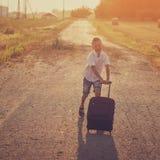 Der glückliche Junge laufen mit einem Koffer in einem Sommer Lizenzfreies Stockfoto