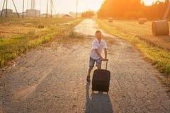 Der glückliche Junge laufen mit einem Koffer an einem sonnigen Tag des Sommers Lizenzfreies Stockfoto
