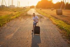Der glückliche Junge laufen mit einem Koffer an einem sonnigen Tag des Sommers Stockbilder