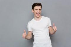 Der glückliche junge Mann, der Daumen gibt, up Zeichen und das Blinzeln Stockfotografie