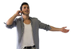 Der glückliche junge Mann, der am Handy mit den Armen spricht, öffnen sich Stockfoto