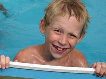 Der glückliche Junge schaut aus dem Pool heraus. Stockfoto