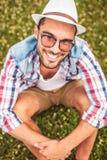 Der glückliche junge zufällige lachende Mann und schaut oben Stockbild