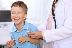 Der glückliche kleine Junge, der Spaß hat, während ist, überprüfen durch Doktor durch Stethoskop Gesundheitswesen, Versicherung u Stockbild