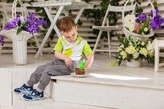 Der glückliche Kleinkindjunge, der seinen Geburtstag feiert, hält das Stück des Kuchens, Innen Geburtstagsfeier für Kinder sorglo Lizenzfreies Stockfoto