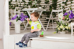 Der glückliche Kleinkindjunge, der seinen Geburtstag feiert, hält das Stück des Kuchens, Innen Geburtstagsfeier für Kinder sorglo Lizenzfreie Stockbilder