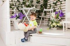 Der glückliche Kleinkindjunge, der seinen Geburtstag feiert, hält das Stück des Kuchens, Innen Geburtstagsfeier für Kinder sorglo Stockbild