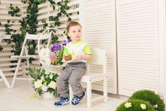 Der glückliche Kleinkindjunge, der seinen Geburtstag feiert, hält das Stück des Kuchens, Innen Geburtstagsfeier für Kinder sorglo Stockfotos