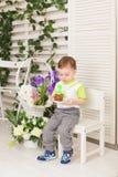 Der glückliche Kleinkindjunge, der seinen Geburtstag feiert, hält das Stück des Kuchens, Innen Geburtstagsfeier für Kinder sorglo Stockfotografie