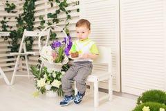Der glückliche Kleinkindjunge, der seinen Geburtstag feiert, hält das Stück des Kuchens, Innen Geburtstagsfeier für Kinder sorglo Stockfoto