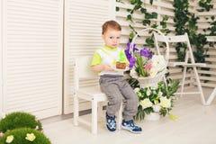 Der glückliche Kleinkindjunge, der seinen Geburtstag feiert, hält das Stück des Kuchens, Innen Geburtstagsfeier für Kinder sorglo Stockbilder
