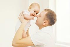Der glückliche lächelnde Vater der Porträtnahaufnahme, der an hält, übergibt sein Baby Lizenzfreie Stockbilder