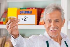 Der glückliche männliche Inhaber, der Rabatt zeigt, unterzeichnen herein Speicher Stockfotos