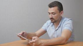 Der glückliche Mann in der Verwunderung benutzt eine Tablette stock video