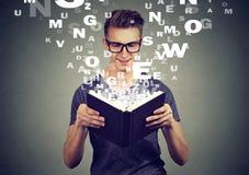 Der glückliche Mann, der ein Buch mit Alphabet liest, beschriftet des Buches oben fliegen Stockfotos