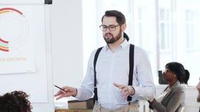 Der glückliche professionelle junge lächelnde Chefmann, der Verkäufe erklärt, stellen auf flipchart zum Team auf modernes Bürosem stock video
