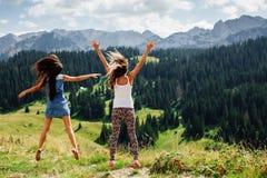 Der glückliche Sprung von zwei Mädchen in den Bergen unterstützen Ansicht Stockbild