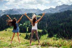 Der glückliche Sprung von zwei Mädchen in den Bergen unterstützen Ansicht Stockbilder