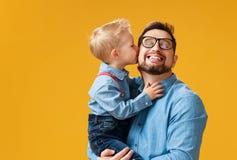 Der glückliche Vatertag! netter Vati und Sohn, die auf gelbem Hintergrund umarmt stockfoto