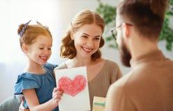 Der gl?ckliche Vatertag! Familienmutter und -tochter Vati begl?ckw?nschen und Geschenk geben stockbild