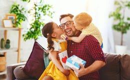 Der gl?ckliche Vatertag! Kinder begl?ckw?nscht Vati und gibt ihm Geschenk und Postkarte lizenzfreie stockfotografie