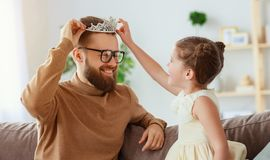 Der gl?ckliche Vatertag! Kindertochter in der Krone tut Make-up Vati an lizenzfreie stockfotografie