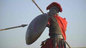 Der Gladiator in der Rüstung und im Sturzhelm wies den Angriff mit einem Schild und die Schläge mit einer Stange, Zeitlupe ab stock video footage