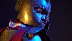 Der Gladiator in seinem Sturzhelm und in roten Mantel steht mit seiner Rückseite und betrachtet zurück der Kamera stock footage