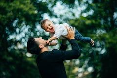 Der glückliche frohe Vater, der Spaß hat, wirft in der Luft sein kleines Kind Lizenzfreie Stockbilder