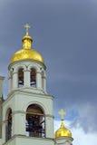 Der Glockenturm der Kirche ein Hintergrund von Sturmwolken Lizenzfreies Stockbild