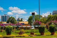 Der Glockenturm und die Blumen, im Abstand der Tempel BEM Kanada Hügel Miri-Stadt, Borneo, Sarawak, Malaysia Stockfotos