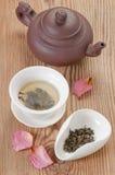 Der grüne Tee, der in der Teeschüssel und -teeblättern gebraut wurde, diente auf rustikaler Holztisch verzierten rosafarbenen Blu Lizenzfreie Stockbilder