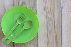 Der grüne Teller, der auf Bretterboden leer ist und haben Kopienraum stockfotografie