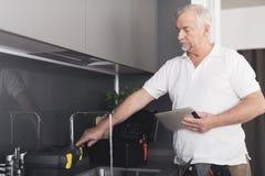 Der graue Klempner steht in der Küche nahe bei dem Hahn Er überprüft die Arbeit des Kranes und hält eine graue Tablette in seinen Stockfotos