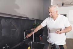 Der graue Klempner steht in der Küche nahe bei dem Hahn Er überprüft die Arbeit des Kranes und hält eine graue Tablette in seinen Stockfotografie