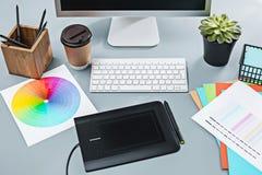 Der graue Schreibtisch mit Laptop, Notizblock mit Leerbeleg, Topf der Blume, Griffel und Tablette für das Überarbeiten Stockbilder