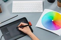 Der graue Schreibtisch mit Laptop, Notizblock mit Leerbeleg, Topf der Blume, Griffel und Tablette für das Überarbeiten Lizenzfreie Stockfotos