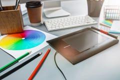 Der graue Schreibtisch mit Laptop, Notizblock mit Leerbeleg, Topf der Blume, Griffel und Tablette für das Überarbeiten Lizenzfreie Stockfotografie