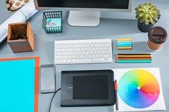 Der graue Schreibtisch mit Laptop, Notizblock mit Leerbeleg, Topf der Blume, Griffel und Tablette für das Überarbeiten Stockfotos