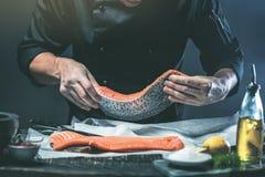 Der große Lachs ist in den Händen des Chefkochs Er benutzt ein Messer, um Lachsfilet zu schneiden stockfoto