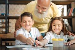 Der Großvater, der entzückende kleine Geschwister aufpasst, wählen Aquarelle Lizenzfreie Stockfotos