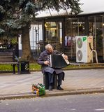 Der Großvater mit einem Akkordeon sitzt und spielt Russland, Krasnodar, Oktober 7,2018 lizenzfreie stockbilder