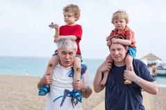 Der Großvater und Vater, die zwei Jungen geben, fahren auf Schultern Stockfotografie