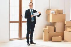 Der Grundstücksmakler, der Grundstücksmakler hält, unterzeichnen herein neue Wohnung mit Pappschachteln lizenzfreies stockbild