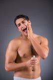 Der gutaussehende Mann, der Aftershave afer Rasieren anwendet Stockfotos