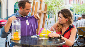 Der gutaussehende Mann, der auf T-Shirt im Café versucht, sitzt er mit seiner Freundin. Stockbild