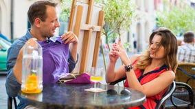 Der gutaussehende Mann, der auf T-Shirt im Café versucht, sitzt er mit seiner Freundin. Lizenzfreies Stockbild