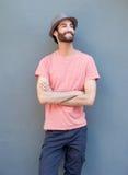 Der gutaussehende Mann, der mit den Armen lächelt, kreuzte auf grauem Hintergrund Stockbild